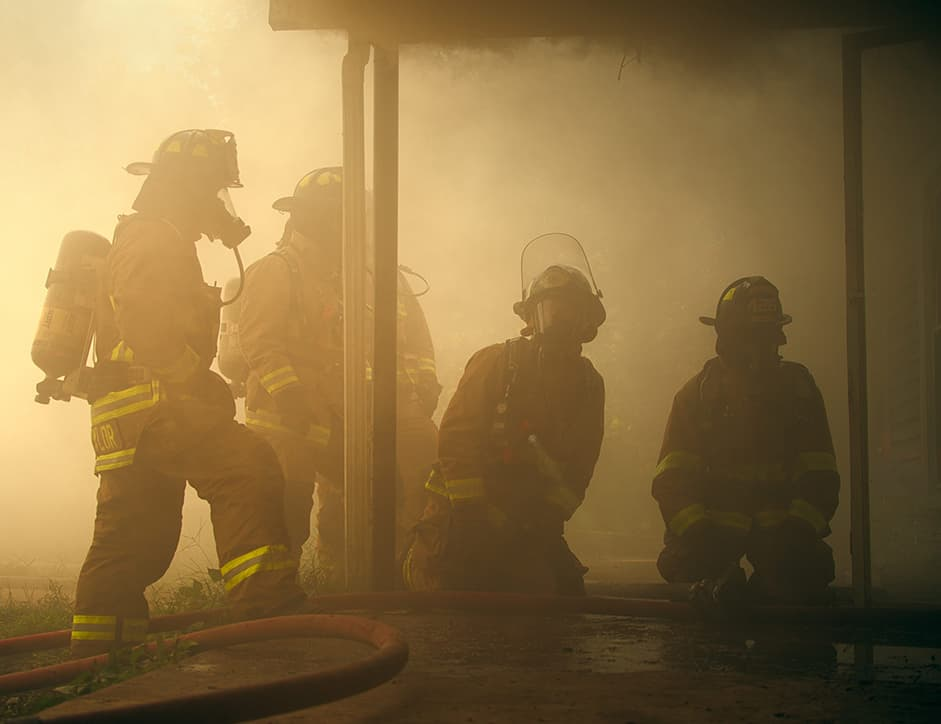 Firefighters standing in smoke